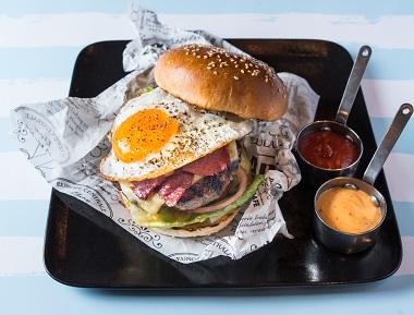 עסקית המבורגר אמריקאי, 250 גרם בשר בקר טרי, מוגש בלחמניית המבורגר עם חסה, עגבנייה, מלפפון חמוץ ובצל סגול, מוגש עם מנה ראשונה ותוספת לבחירה.