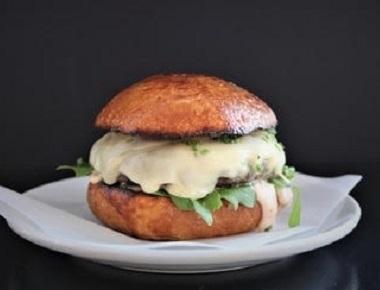 המבורגר Raclette, בשר בקר, גבינת רקלט שווייצרית, עירית, רוטב ברביקיו ביתי ועלי רוקט.