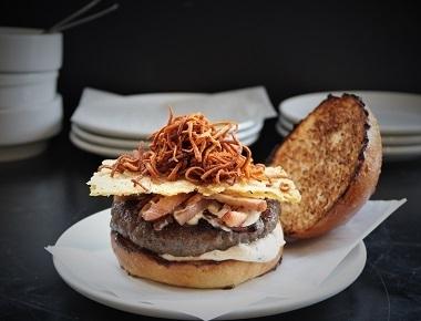 המבורגר La Truffe, בשר בקר, איולי כמהין, חזה אווז מעושן, טוויל גבינת פרמזן וגפרורי בטטה קריספית.