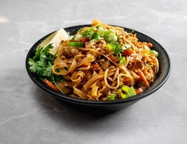 pad thai chicken, רוטב חמוץ מתוק, אטריות אורז, ביצה, רצועות עוף, כרוב גזר, נבטים, בצל ירוק, כוסברה, בוטנים קצוצים ופלח לימון.