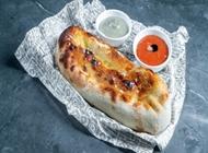 פוקצ'ה, לחם איטלקי אפוי בתנור אבן עם שמן זית, שום ודבש, לצד קרם חצילים וסלסת עגבניות טריות.