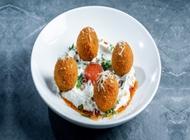 ארנצ'יני, כדורי ריזוטו במילוי מוצרלה, מנצ'גו וכמהין, מוגש על מצע קרם פרש, שמן זית, סלסת עגבניות, זיתי קלמטה ופרמז'ן.