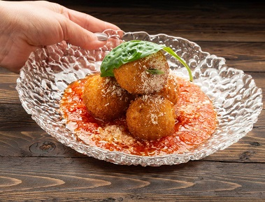 ארנצ'יני, כדורי ריזוטו, מוצרלה ופרמז'ן, בציפוי פריך עם רוטב עגבניות.