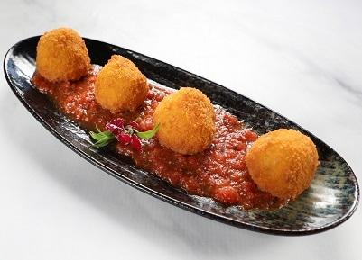 ארנצ'יני מטוגן, כדורי ריזוטו פריכים במילוי עשבי תיבול טריים וגבינת מוצרלה לצד רוטב עגבניות בנגיעת פסטו.