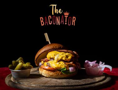 המבורגר - THE BACONATOR, שתי קציצות 110 גרם עם רצועות בייקון או בייקון בקר וצ'דר ביניהן ומעליהן, בלחמניית בריוש, חסה, עגבנייה ובצל סגול.