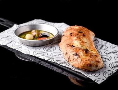 פוקצ'ה טאבון, מוגש עם מטבל שמן זית, בלסמי, עגבניות מרוסקות ושום קונפי.